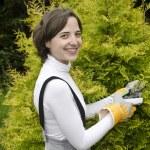 mujer joven con la herramienta de jardín en jardinería — Foto de Stock