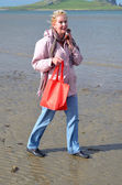 Woman walks with a red bag on a beach — Stock Photo