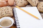 Healthy rolls and a booklet for notes — Stock Photo