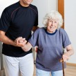 Trainer Assisting Woman With Walking Stick - Stock Photo