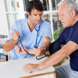 Stock Photo: Male Nurse Checking Blood Pressure Of a Senior Patient