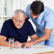 Male Nurse Helping Senior Man In Solving Puzzle - Foto Stock