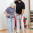 Stock Photo: Trainer Assisting Senior WomIn Moving