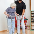 Trainer Assisting Senior Woman In Moving — Stock Photo