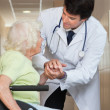 Stock Photo: Doctor Comforting Senior Patient At Hospital