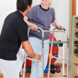 Stock Photo: Woman With Walker Looking At Trainer