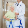 Doctor Helping An Old Woman With Her Walker - Stock Photo