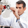 Eye Doctor Checking Lens Of Trial Frames - Photo