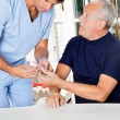 Male Nurse Checking Sugar Level Of Senior Man — Stock Photo #10767681