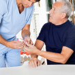 Male Nurse Checking Sugar Level Of Senior Man - Stock Photo