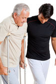 Trainer Helping Senior Man With Crutches — Stock Photo