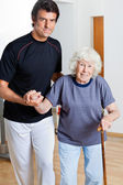 Trainer Assisting Woman With Walking Stick — Stock Photo