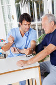 Male Nurse Checking Blood Pressure Of a Senior Patient — Stock Photo