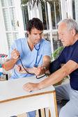 Comprobación de la presión arterial de un paciente senior masculina de la enfermera — Foto de Stock