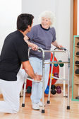 Woman With Walker Looking At Trainer — Stock Photo