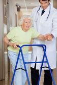 Lekarz pokazuje drogę do pacjenta za pomocą walkera — Zdjęcie stockowe