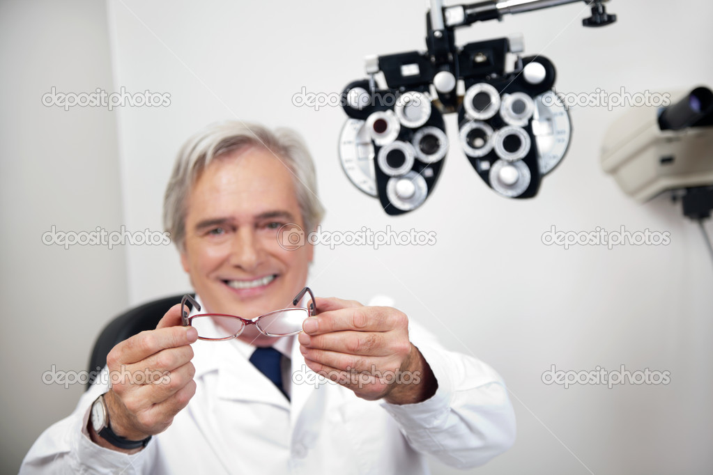 Portrait of smiling mature optometrist holding glasses at the clinic — Stock Photo #10761178
