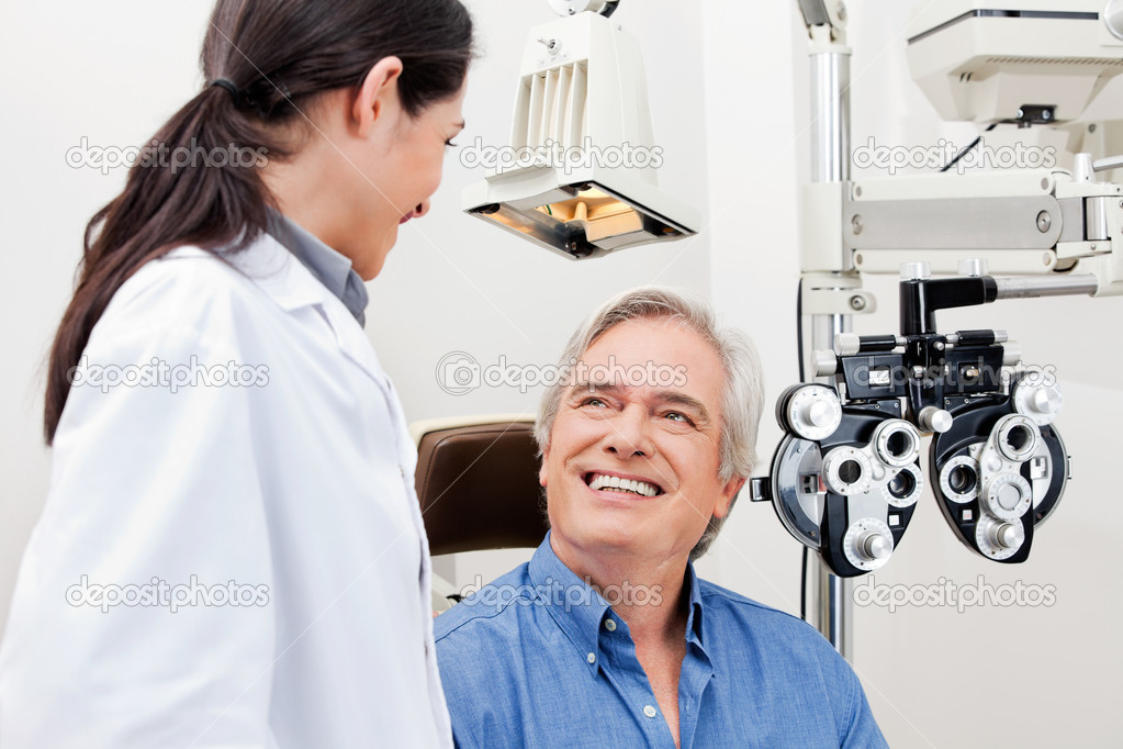 Smiling mature patient consulting with optometrist for an eye checkup — Stock Photo #10761582