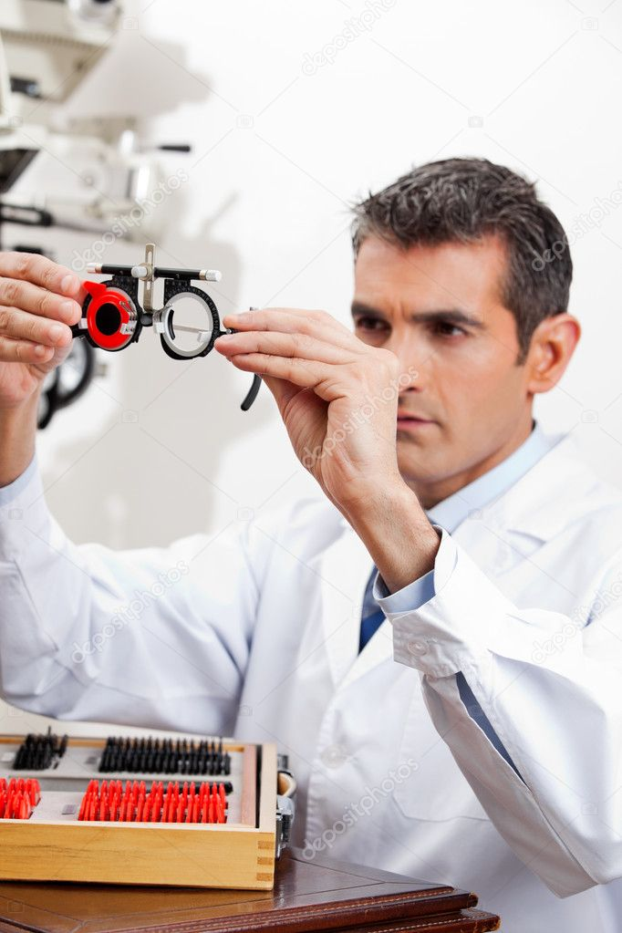 Optometrist checking the lens of trial frames with concentration for eye examination — Stock Photo #10767605