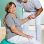 Therapist Helping Senior Woman Sitting On Fitness Ball — Stock Photo #10871439