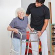 Senior Woman Holding Walker While Trainer Assisting Her - Stock Photo