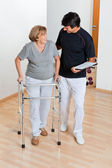Trainer Looking At Senior Woman Using Walker — Stock Photo