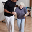 Stock Photo: Therapist helping Patient To Walk