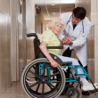 Doctor with Patient on Wheel Chair — Stock Photo #11201683