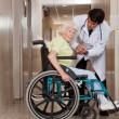 Stock Photo: Doctor with Patient on Wheel Chair