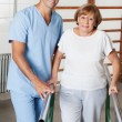 Therapist Assisting Senior Woman To Walk With The Support Of Bar — Foto de Stock