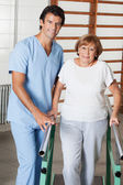 Therapist Assisting Senior Woman To Walk With The Support Of Bar — Stock Photo