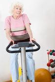 Gelukkig senior vrouw uitoefenen op fiets — Stockfoto