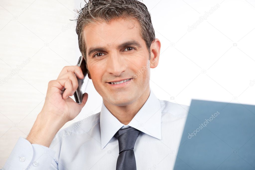 Businessman talking on cell phone at work isolated on white background.  Stock Photo #11200576