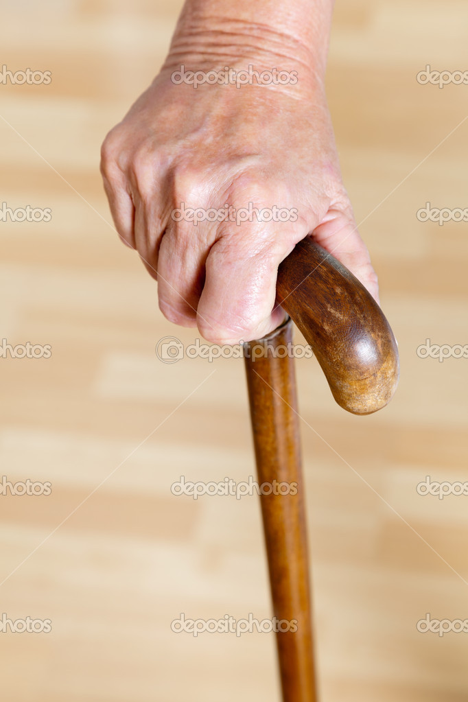 Close-up of woman's hand holding wooden walking stick — Stock Photo #11204550