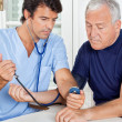 Male Nurse Checking Blood Pressure Of a Senior Man — Stock Photo #11228013