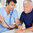 Male Nurse Checking Blood Pressure Of a Senior Man — Stock Photo