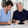 Stock Photo: Mature Man playing Sudoku Puzzle