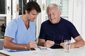 Mature Man playing Sudoku Puzzle — Stockfoto