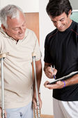 Patient on Crutches and Physician — Stock Photo