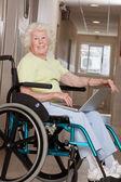 車椅子のラップトップを使用して上の女性 — ストック写真