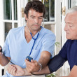 Doctor taking the Blood Pressure - Stock Photo