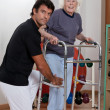 Therapist helping Patient use Walker — Stock Photo #11536337