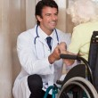Doctor with Patient on Wheel Chair - Zdjęcie stockowe
