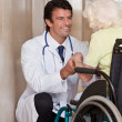 Doctor with Patient on Wheel Chair - Stock Photo