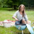 Young Woman Lighting a Barbecue — Stock Photo #11537189