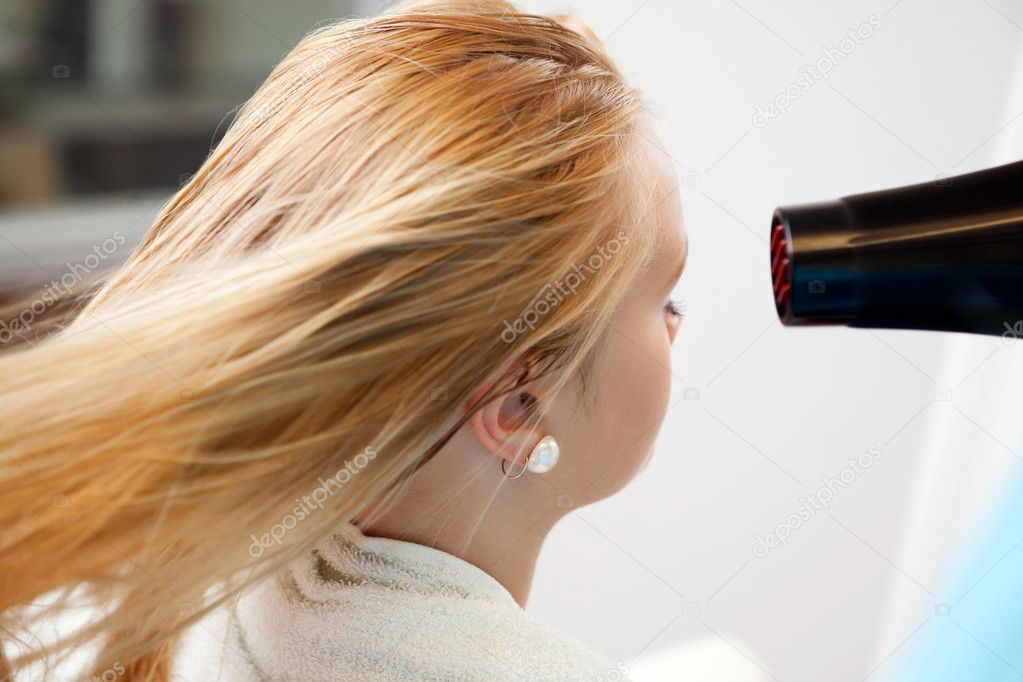 Blond hair of a young woman being dried by blow dryer at parlor — Stock Photo #11659480