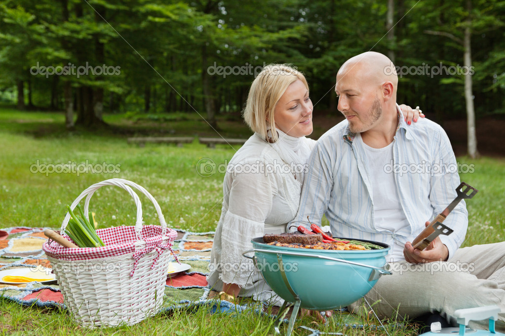 Mature couple in casual clothes looking at each other while on an outdoor picnic in forest park — Stock Photo #11659545