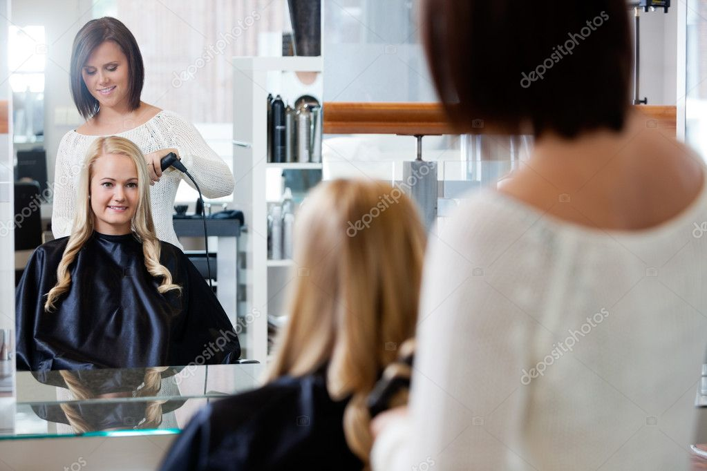 Mirror reflection of young woman getting her curled by stylist at parlor — Stock Photo #11659760