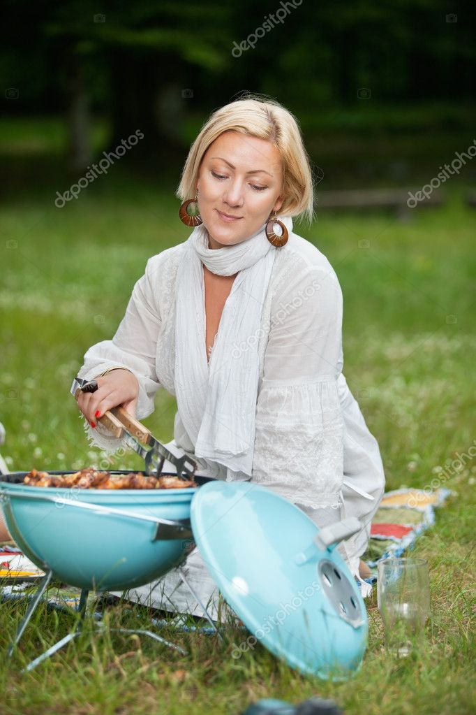 Beautiful mature woman in casual wear cooking food on a portable barbecue on a weekend outing — Stock Photo #11659906