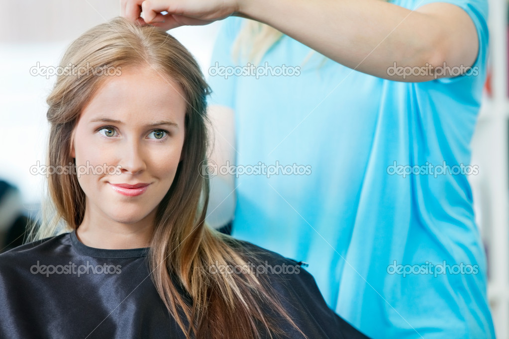 Young woman smiling while hairdresser getting her ready for haircut at parlor — Stock Photo #11660245